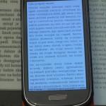 Po lewej ekran e-ink bez podświetlenia, po prawej z lekkim podświetleniem. W środku smartfon.